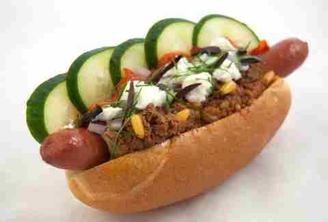 Hot dog with chili, cucumbers and feta cheese