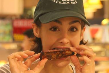 A butcher at Border Springs Farm in Reading Terminal Market eats the ribs