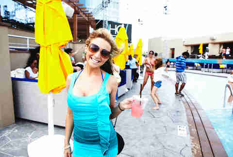 A partygoer at HQ Beach Club at Revel holds a cocktail