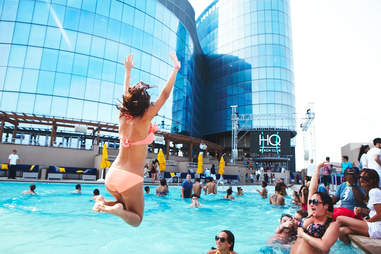 A girl in a bikini jumps in the pool at HQ Beach Club at Revel
