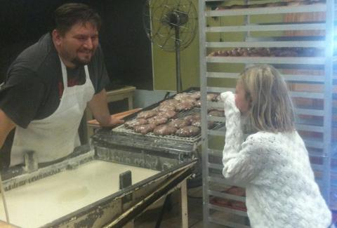 Donuts being prepared as a child watches on at Mel-O-Glaze