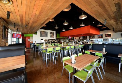 Interior of Hopdoddy with wood floors and ceilings and lime green chairs.
