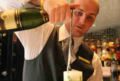A bartender pours champagne with a swizzle at the Library Bar at the Rittenhouse Hotel