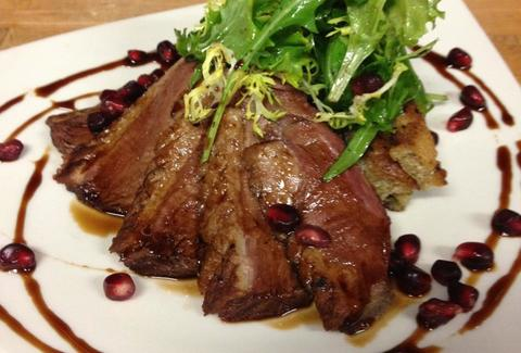 Seared duck, greens, and pomegranate seeds