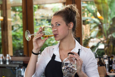 A beautiful waitress drinking smoked tequila