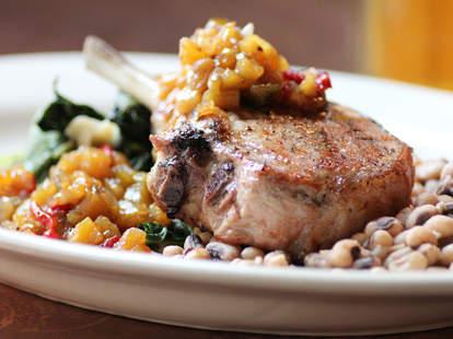 Bone-in grilled pork chop w/ peach relish, collard greens, and black eyed peas at Society on High
