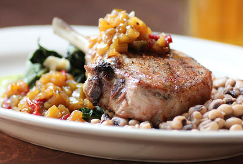 Bone-in grilled pork chop w/ peach relish, collard greens, and black eyed peas at Society on High