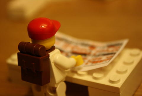 lego person reading paper