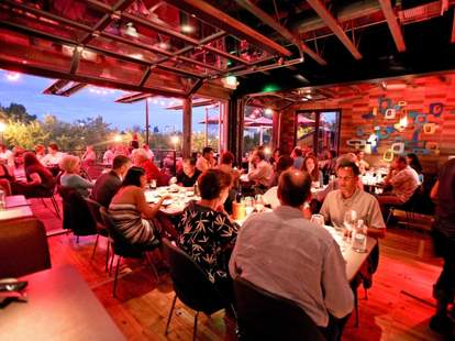 People dining in the dimly lit interior of Root Down with open windows and a view of downtown.