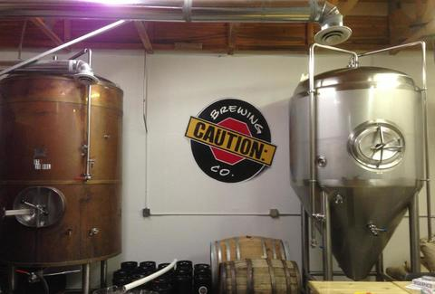 The CAUTION trademark poster hangs on a wall between two brewing machines.