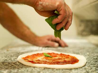 A hand drops fresh basil unto an uncooked pizza smeared with tomato sauce.