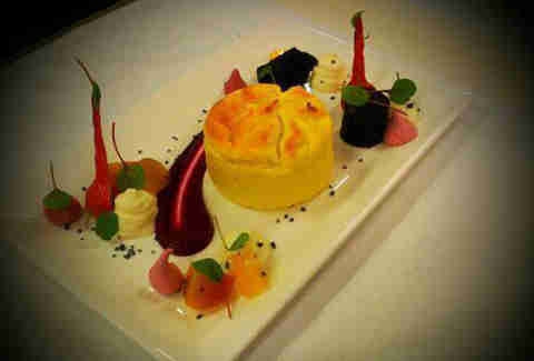 A colorful dish of puff pastry and various jellies on a white plate.