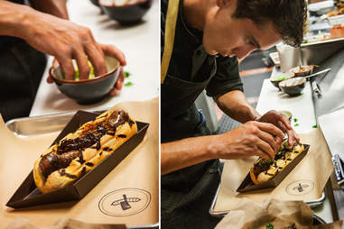 Chef Carlos SanMartano putting toppings on a ribeye sausage at Salt and Cleaver in San Diego.