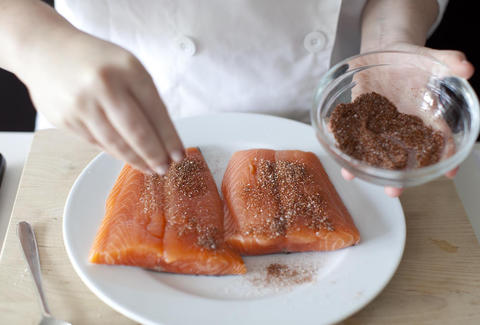 Seasoning a salmon dish from Plated
