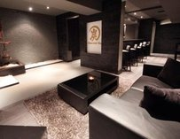Dark interior of charcoal bar, all black and gray with leather couches.