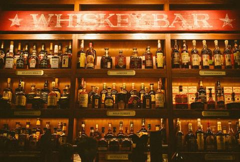 Hundreds of whiskey bottles stocked on three shelves.