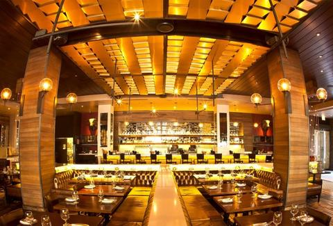 Panoramic of the inside of Tavernita, long tables and a bar in the back, decorated in gold and yellow.