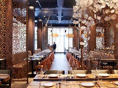 Interior of Embeya decorated in gold metalwork with crystal leaf shaped chandeliers.