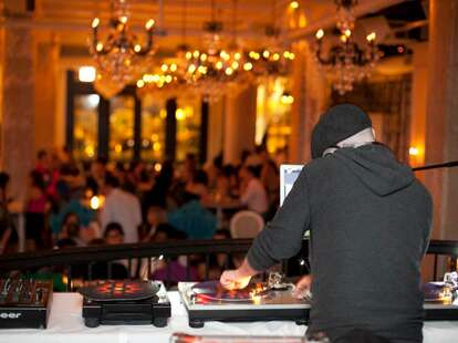 A DJ spins on a raised platform for a crowded room of people under crystal chandeliers.