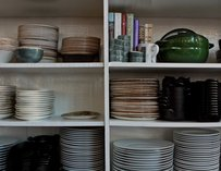 Shelves of green, white and, blue pots and plates.