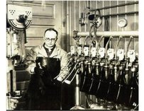 Old time photograph of a man in an apron operating various taps.