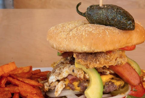 A burger piled high with avocado, peppers and jalapenos.