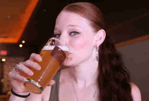 A girl drinks a craft beer at Sto's Bar