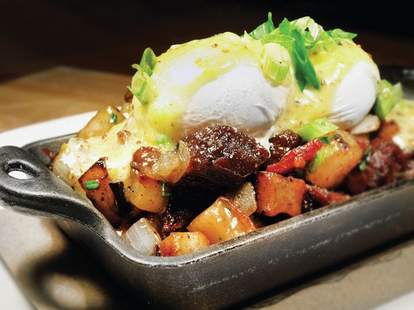 An eggs Benedict piled with potatoes and sour cream.