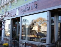 Outside view of Cafe Muse with a small patio and large windows.