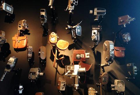 Various types of video cameras hang in dim lighting.