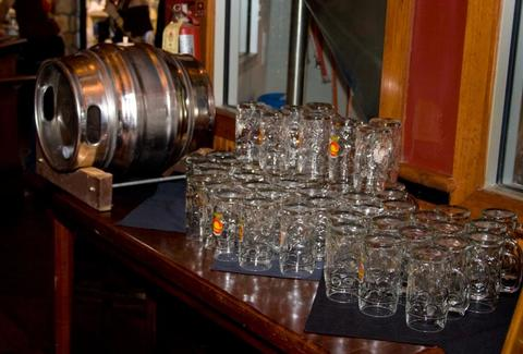 A keg with dozens of glasses next to it