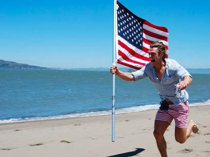 Dude on the beach running with an American flag