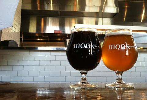 A light and dark beer in two bell shaped Monk beer glasses.