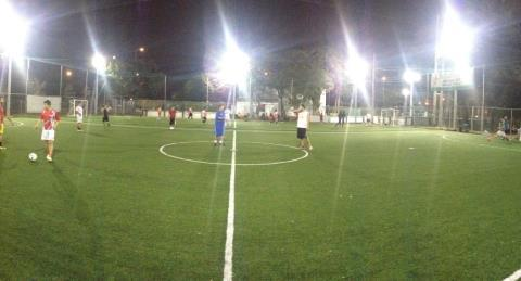 A soccer field at night with several players.