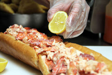 Adding lemon juice to the USS Lobstitution lobster roll at Pauli's North End