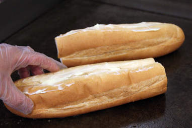 Buttered hoagie roll going on the grill at Pauli's North End