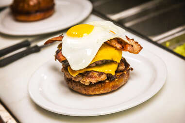Chef tops off the 'Merica Burger with a fried egg at Slater's 50/50 in San Diego.