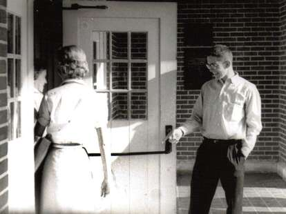 A gentleman with manners opening a door for a lady
