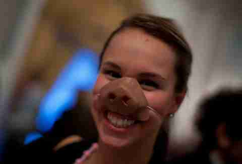 A girl wears a pig snout at a Cochon Epic event