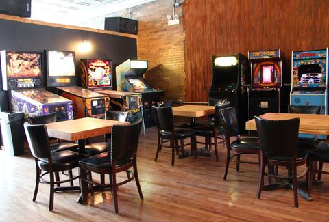 Arcade games line the walls of the bar with black leather chairs and wooden tables.