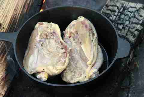 halved chicken in cast-iron pan