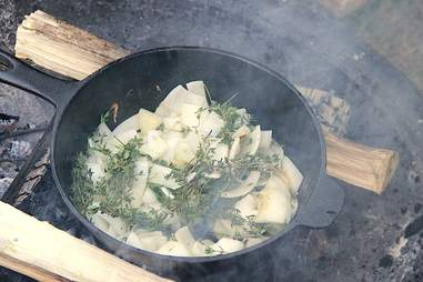 onions and thyme cooking in cast-iron pan