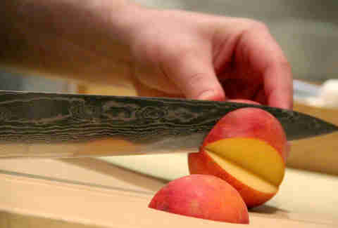 Slicing a peach in the kitchen at The Lambs Club