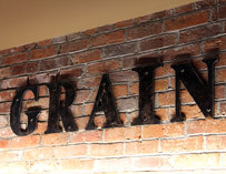 "The letters ""GRAIN"" on a brick wall"