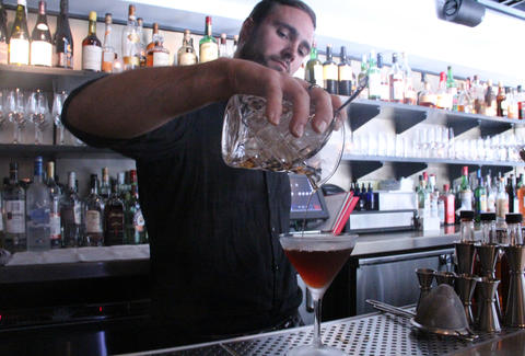 a bartender pours a rye cocktail at a.bar