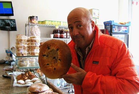 Andrew Zimmern holding some giant bread
