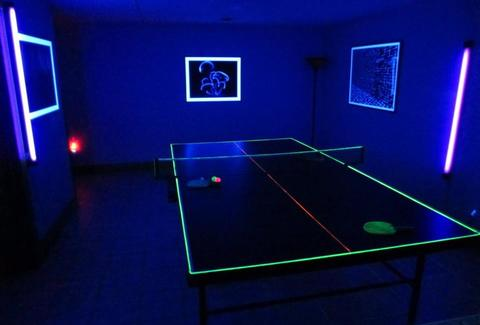 Neon ping-pong table and paddles in the dark