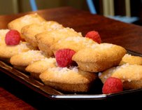 Small pastry cakes with powdered sugar and raspberries.
