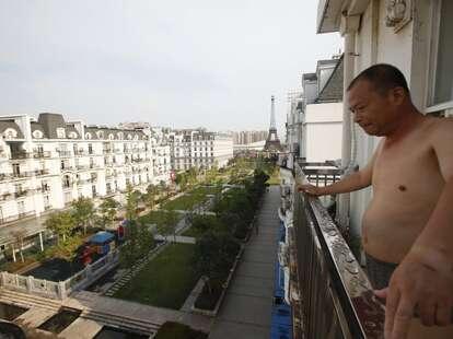 Chinese man on balcony overlooking Tianducheng