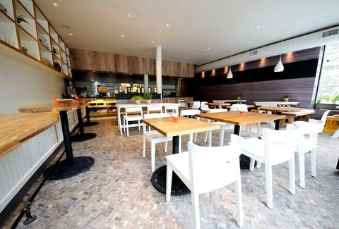 The bright interior at Senza, with various white tables and wooden chairs.